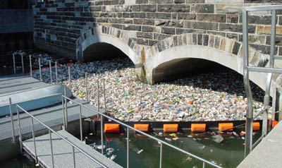 The bridge with masses of trash floating under it, contained by a floating wall